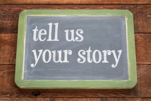 Tell us your story. White chalk text on a vintage slate blackboard against rustic barn wood.